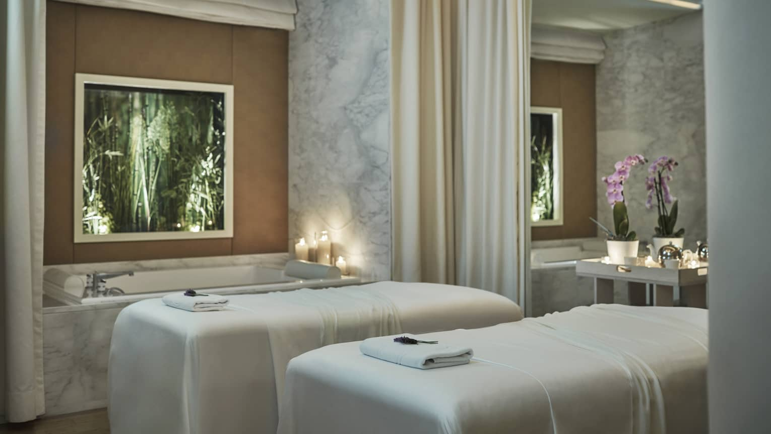 Spa couples massage beds with white sheets by candlelit tub