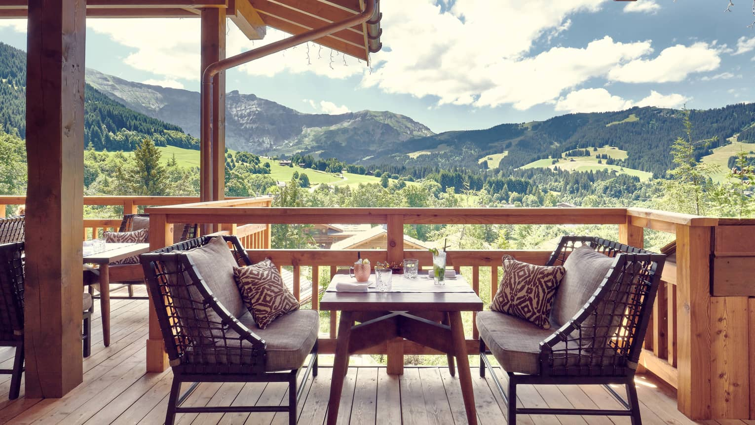 Two cushioned benches with table in middle on wooden terrace with mountain views