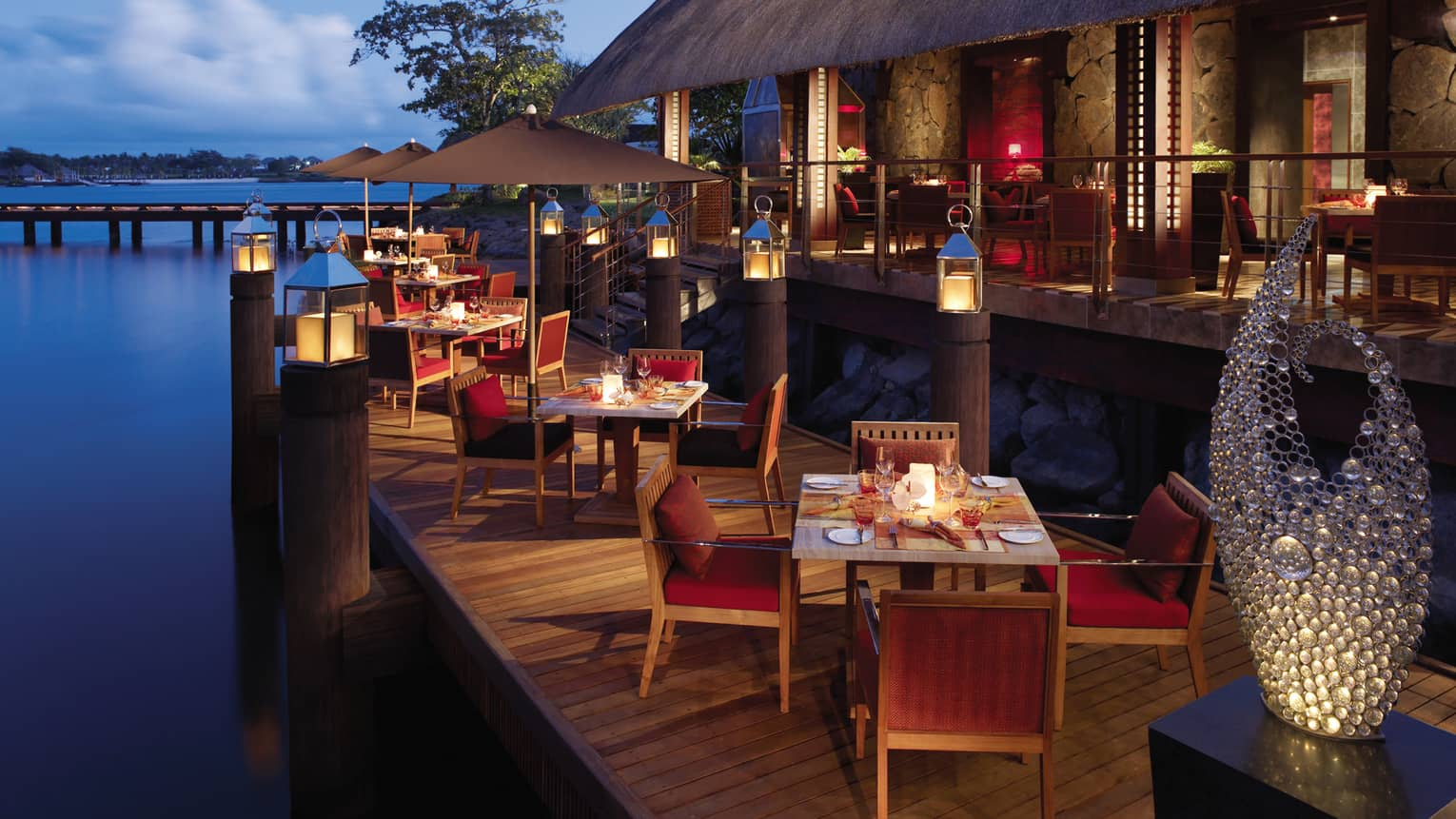 Outdoor dining tables on a pier overlook the waters.