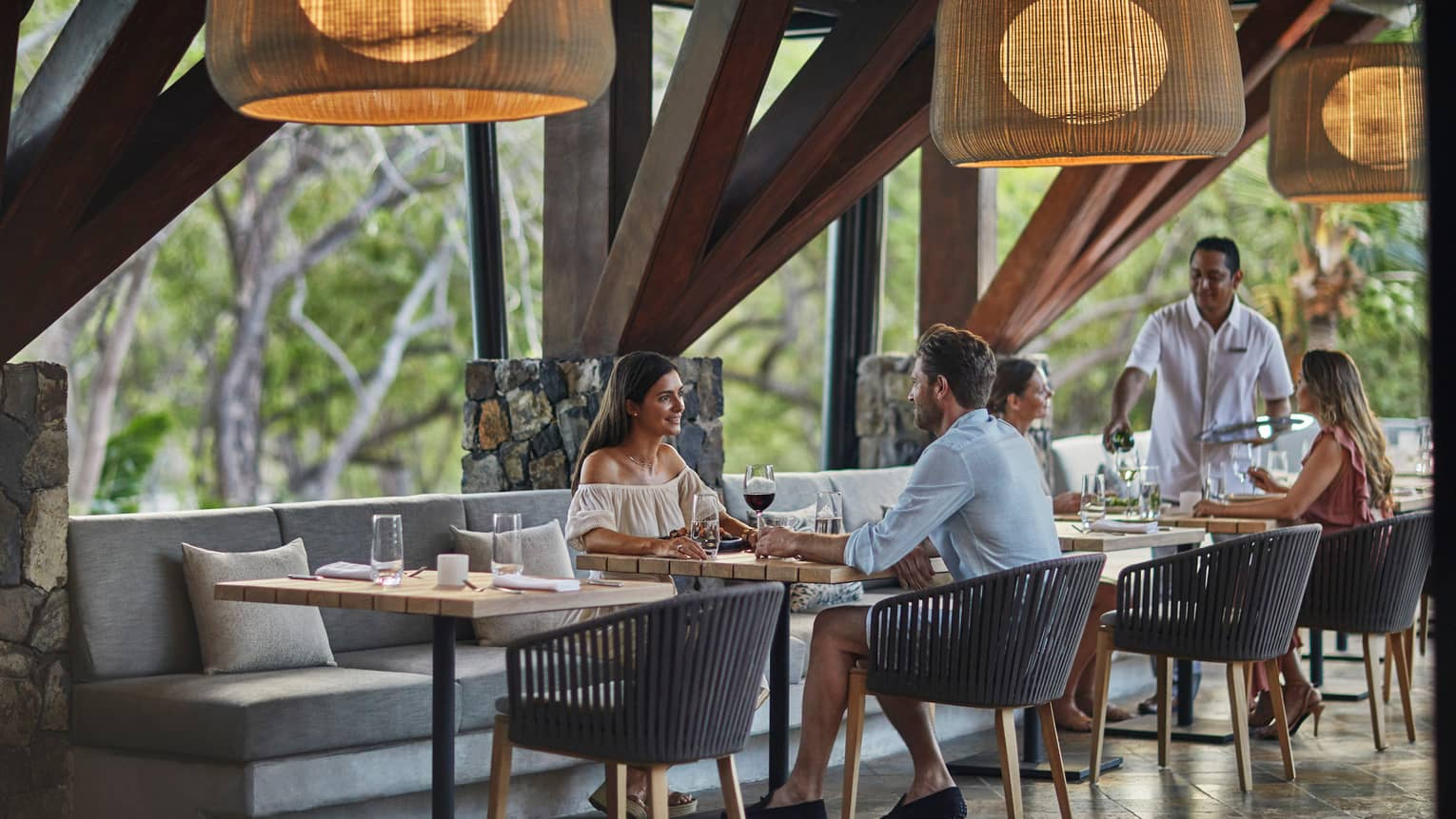 Couples dine at Bahia patio tables on long grey banquette, under large round bamboo lights