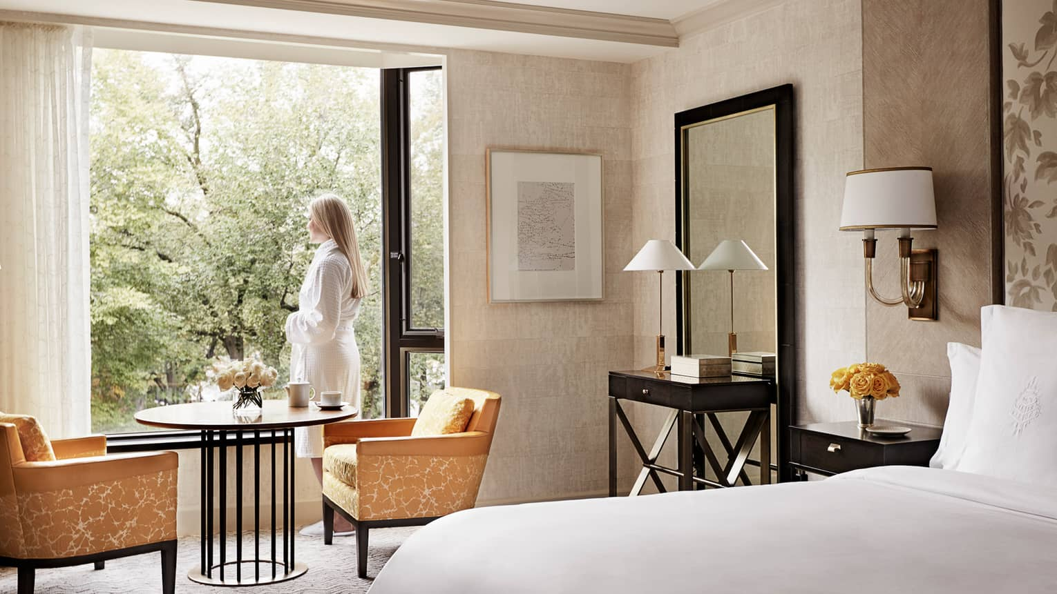 A woman wearing a robe, standing in her pristine room and looking outside the window at lush trees
