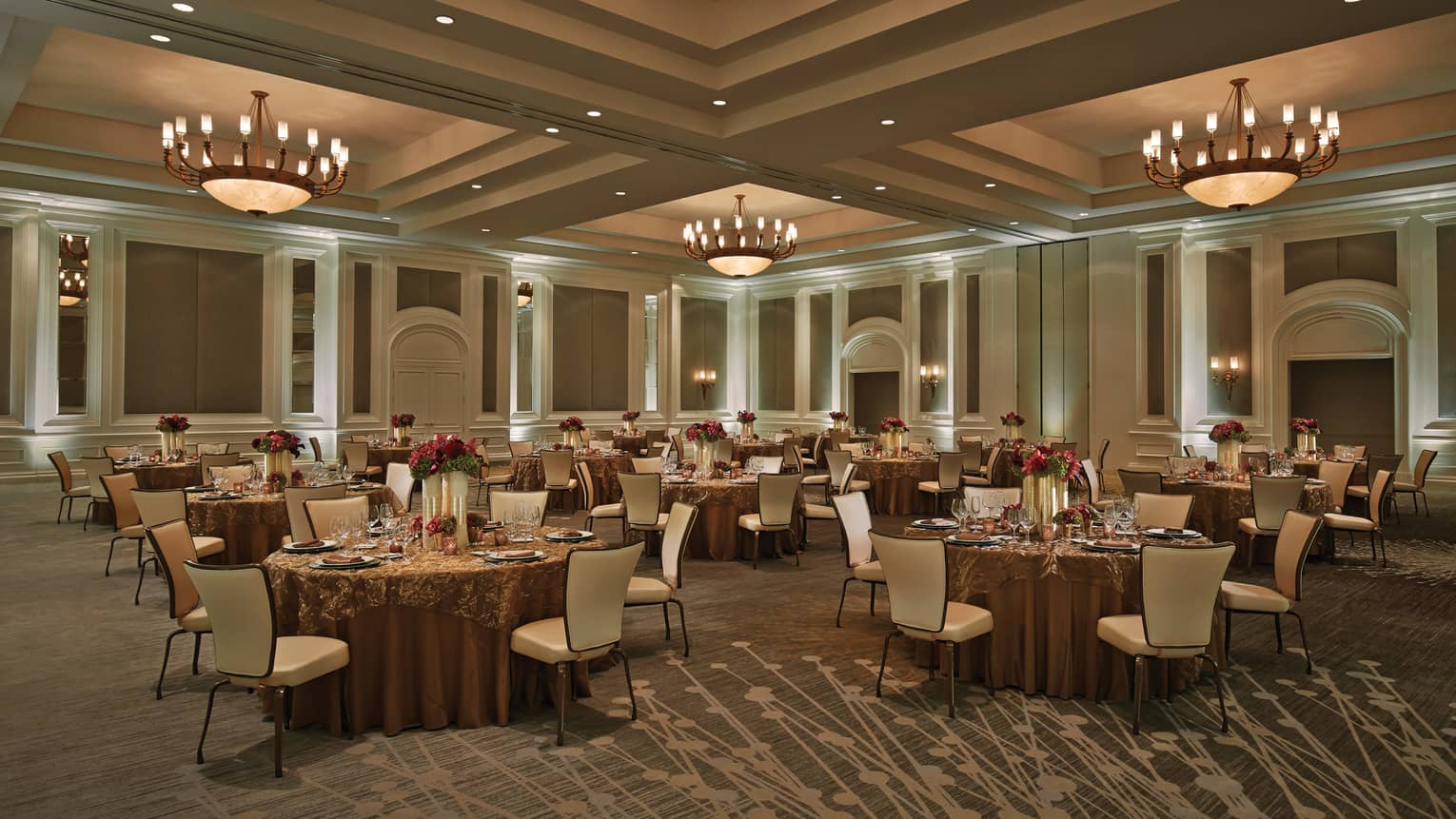 Small round dining tables under large dome lights in Acacia Ballroom