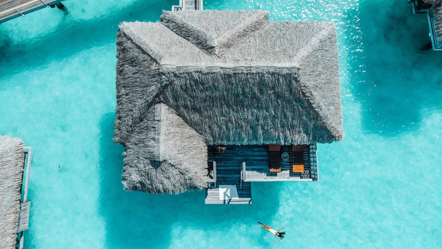 Aerial view of person swimming away from overwater bungalow in turquoise lagoon