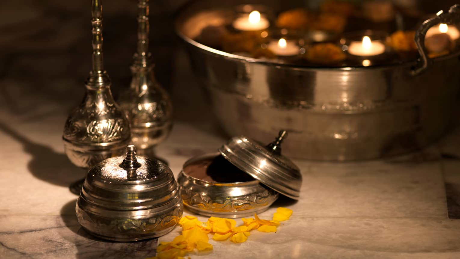 Spa ingredients lay on table with metal containers, a bowl with floating votive candles
