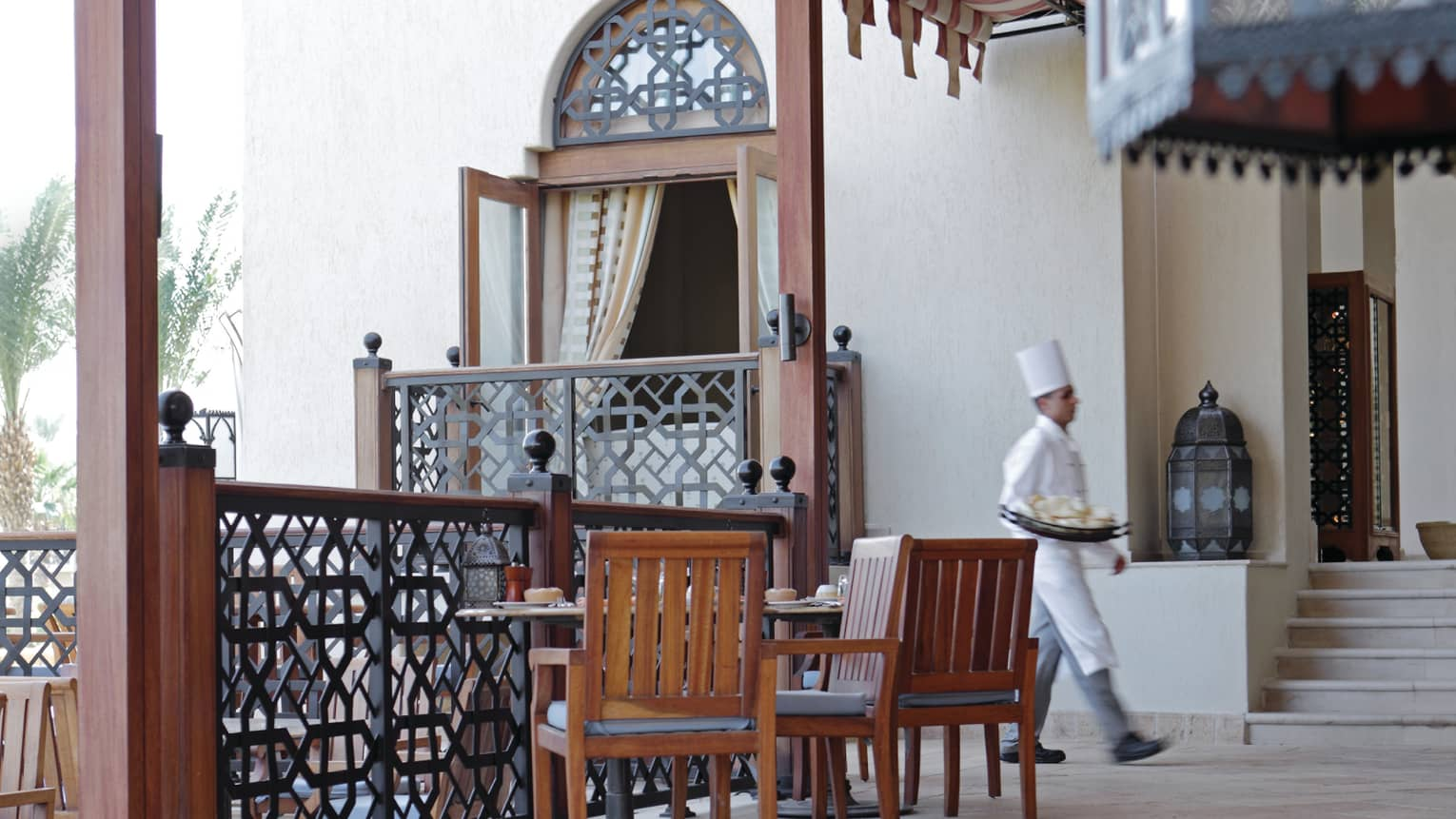 Chef in white uniform walks past wood patio tables, chairs, decorative railing at Arabesque restaurant