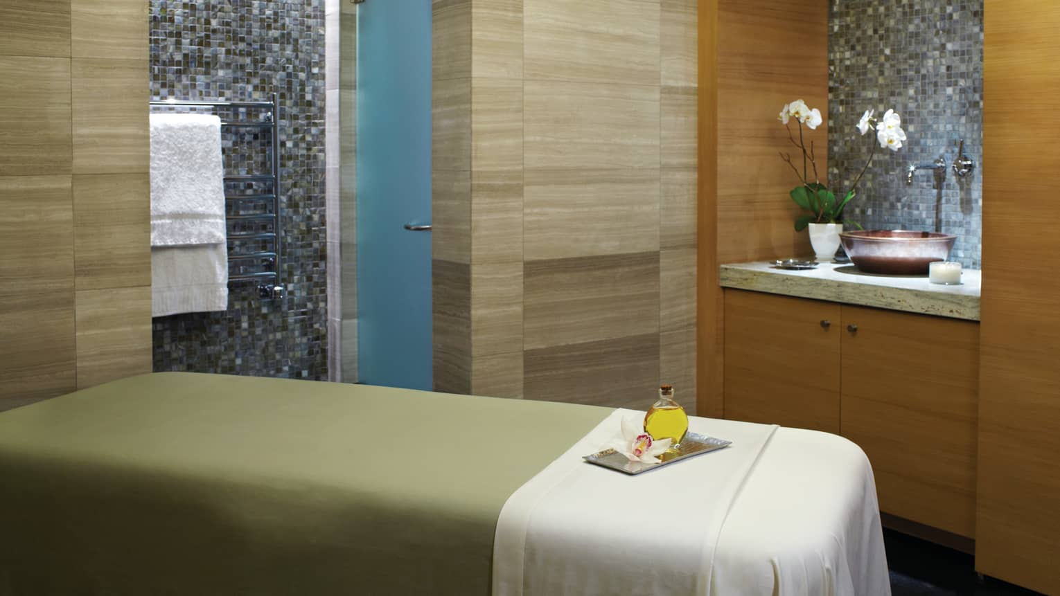 Massage table with green blanket, white sheet, wood and tile walls, sink