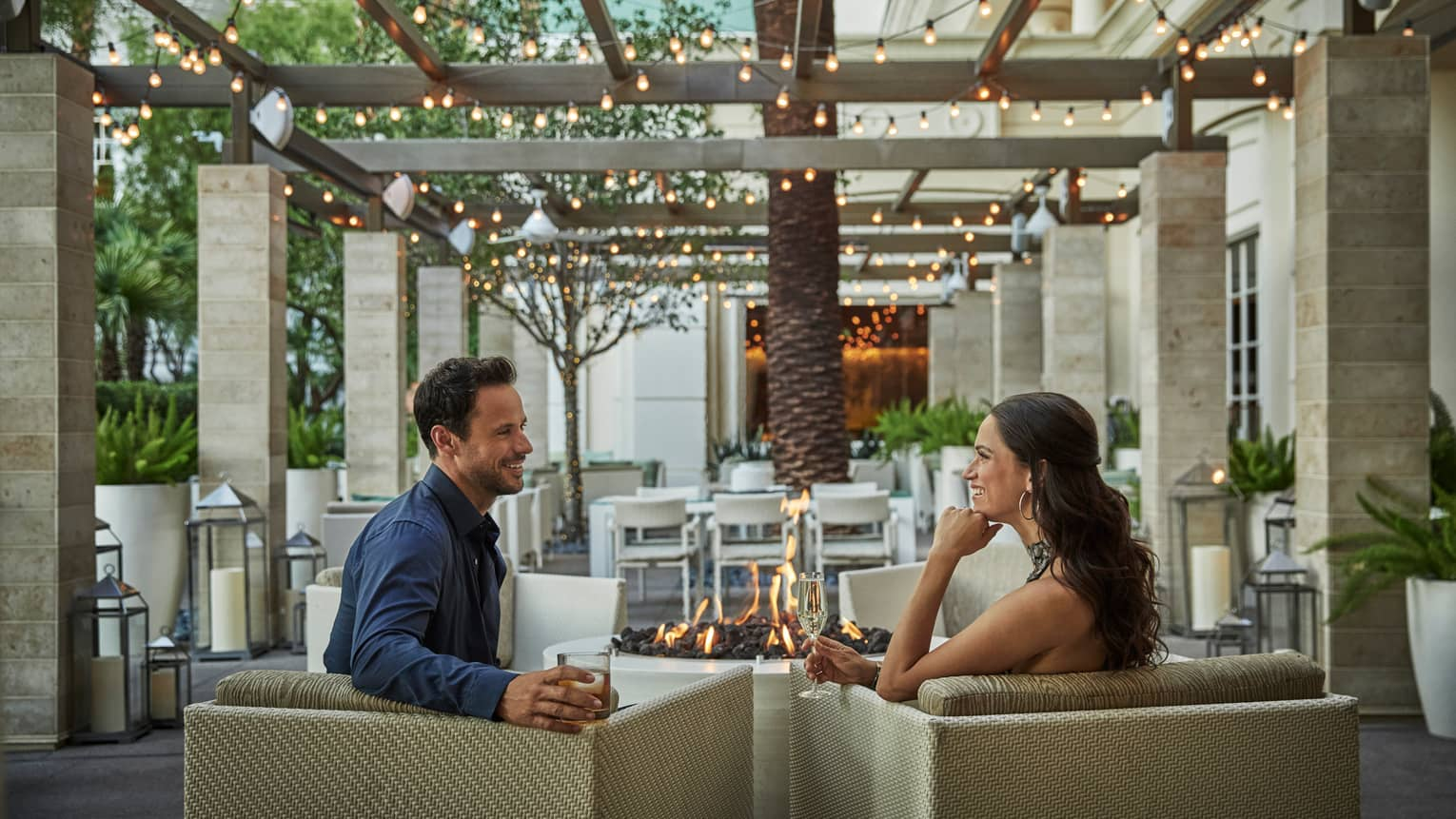 Couple with cocktails sit on patio armchairs by outdoor fireplace under pergola