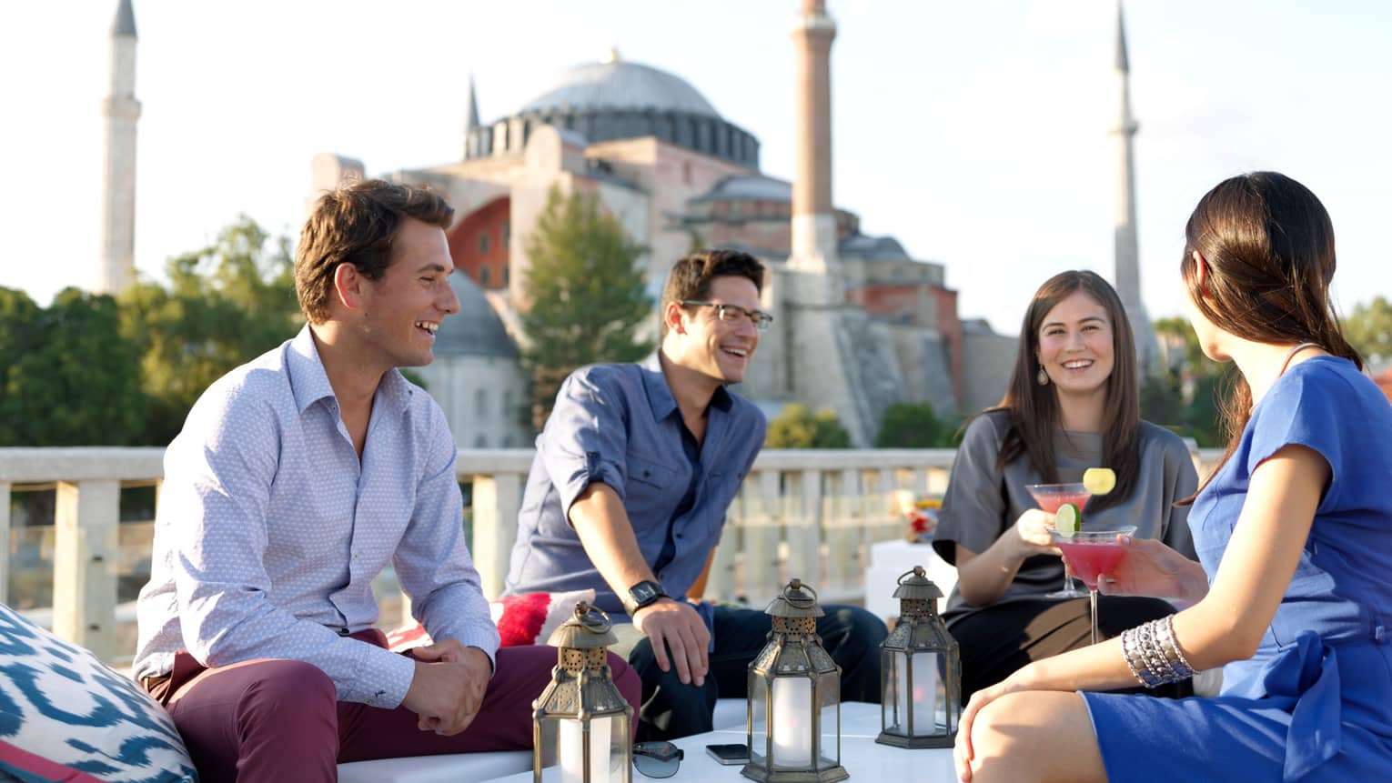 Two men and two women with pink martinis sit on patio in front of balcony, mosque in background