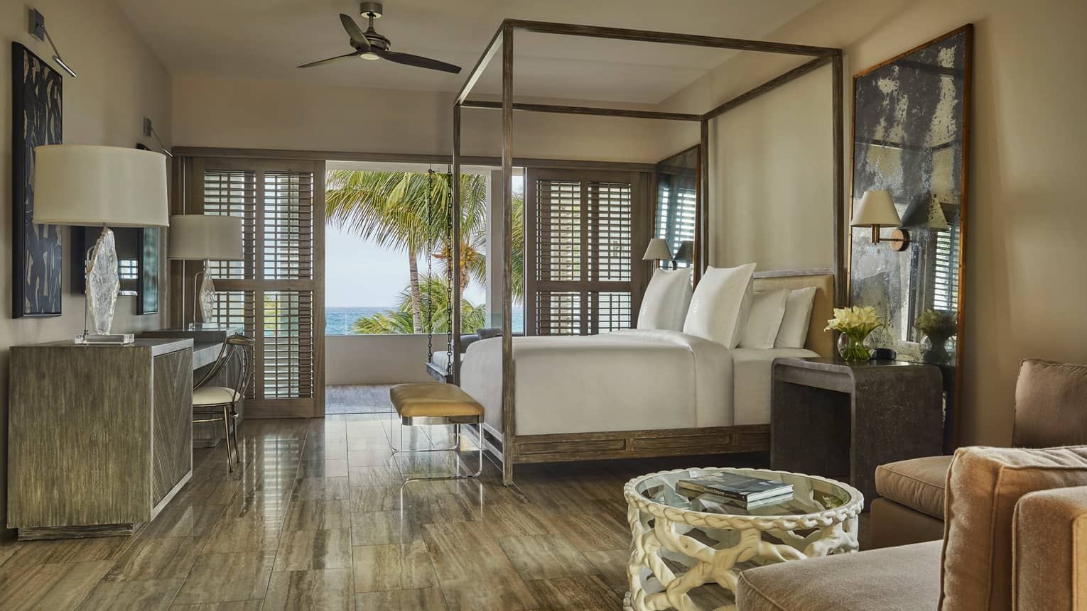 Three-Bedroom Beachfront Villa view from L-shaped sofa to canopy bed, tables with lamps, open patio shutters