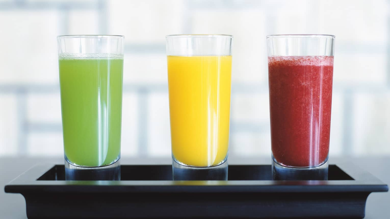 Three tall juice glasses with colourful green, orange and red smoothie drinks on tray