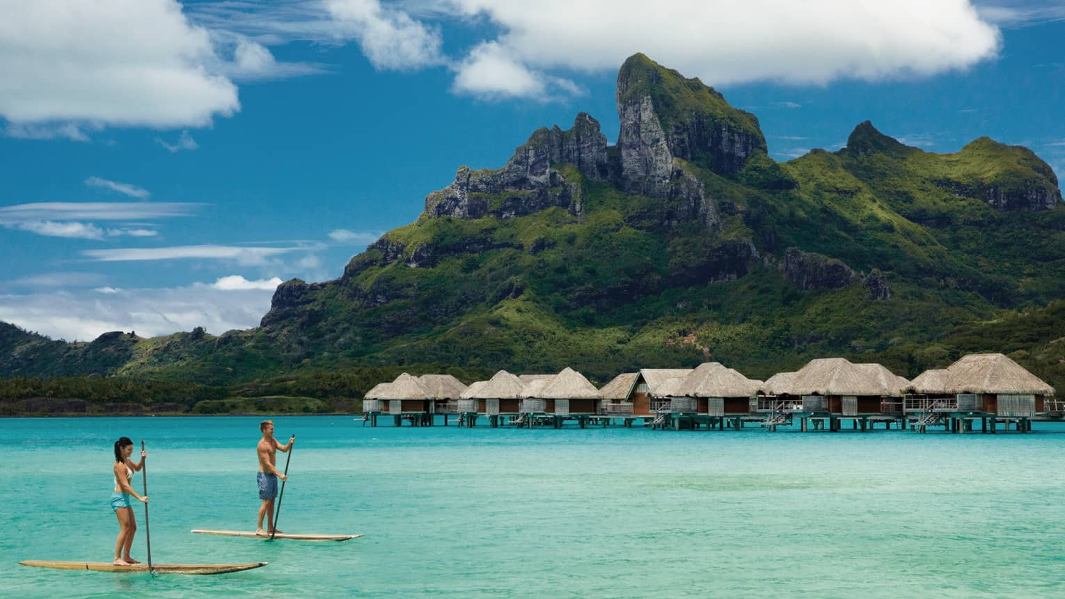Two guests stand-up paddleboarding in a Bora Bora lagoon