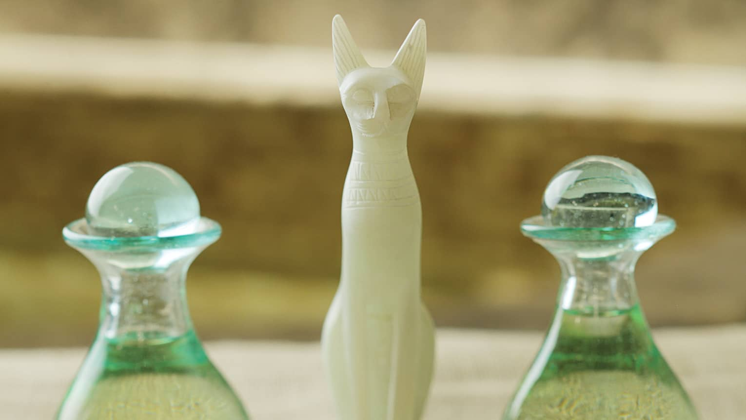 White cat sculpture between two green glass bottles