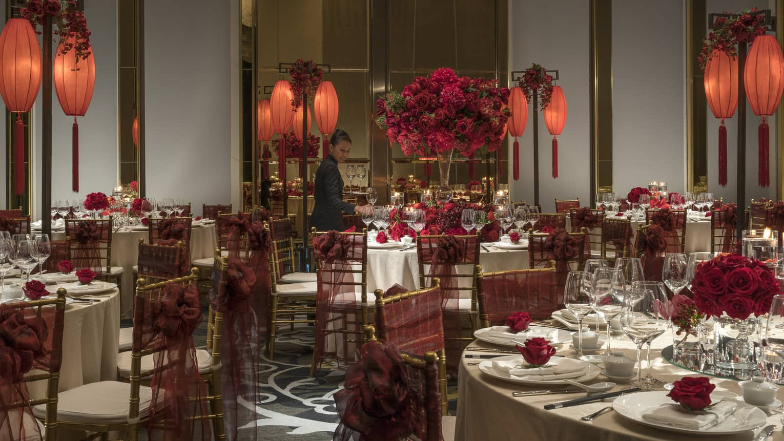 Hotel staff sets large round banquet tables with red flowers, lanterns for Chinese wedding