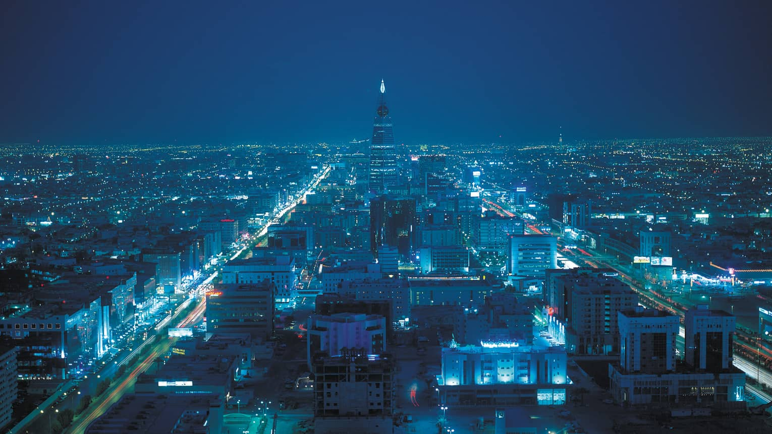 Aerial view of Riyadh buildings and lights at night, blue hues