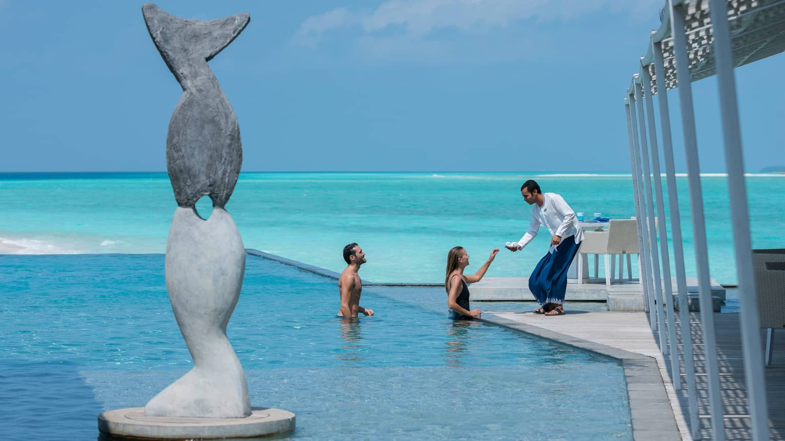 Server passes small towels to man, woman in swimming pool beyond tall stone statue of fish