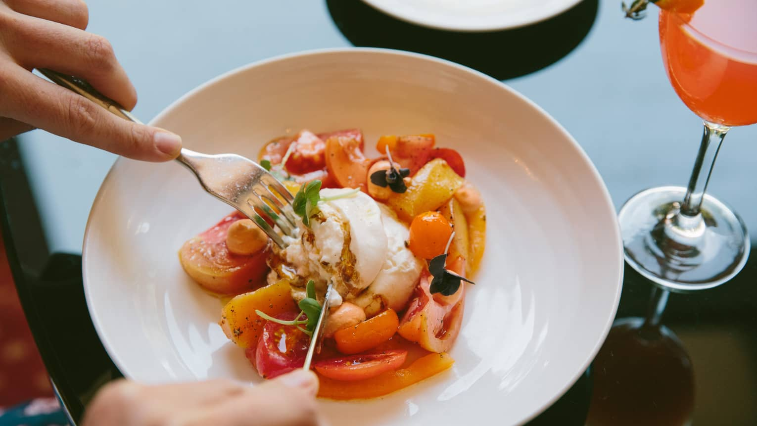Burrata, surrounded by peaches and tomatoes