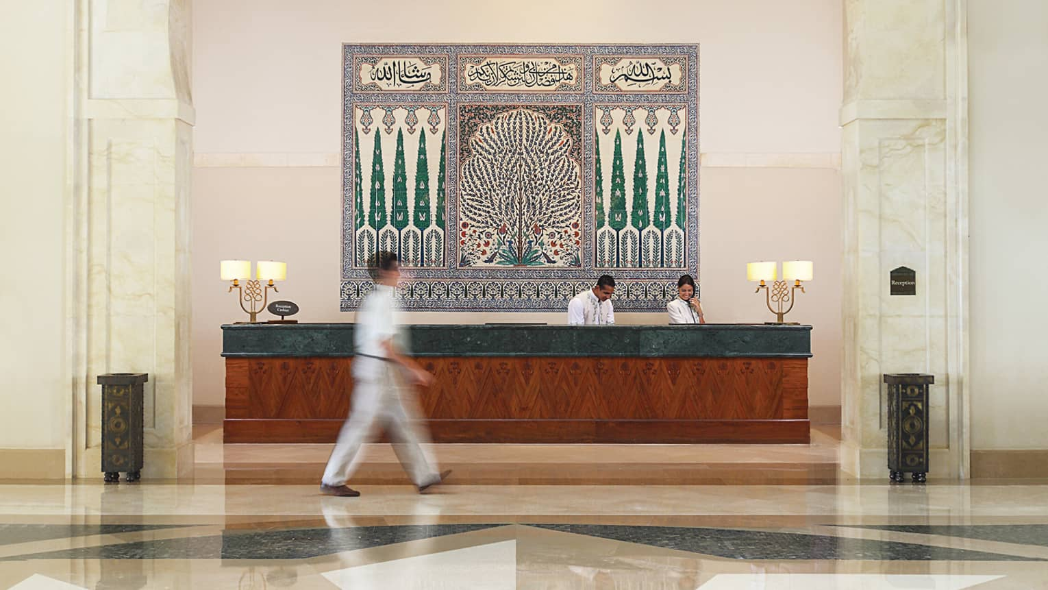 Man walks through hotel lobby, past staff at reception desk under large tile mosaic