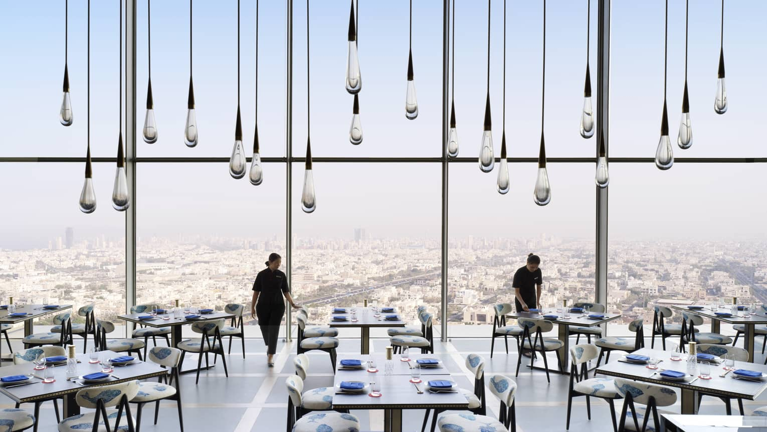 Large glass raindrop-shaped lights hang from soaring ceiling in sunny dining room, servers set tables