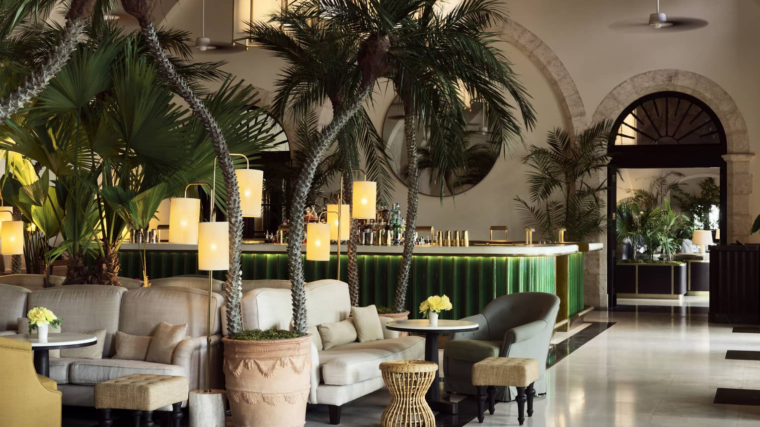 Indoor lounge with palm trees, white upholstered arm chairs, green bar in the background