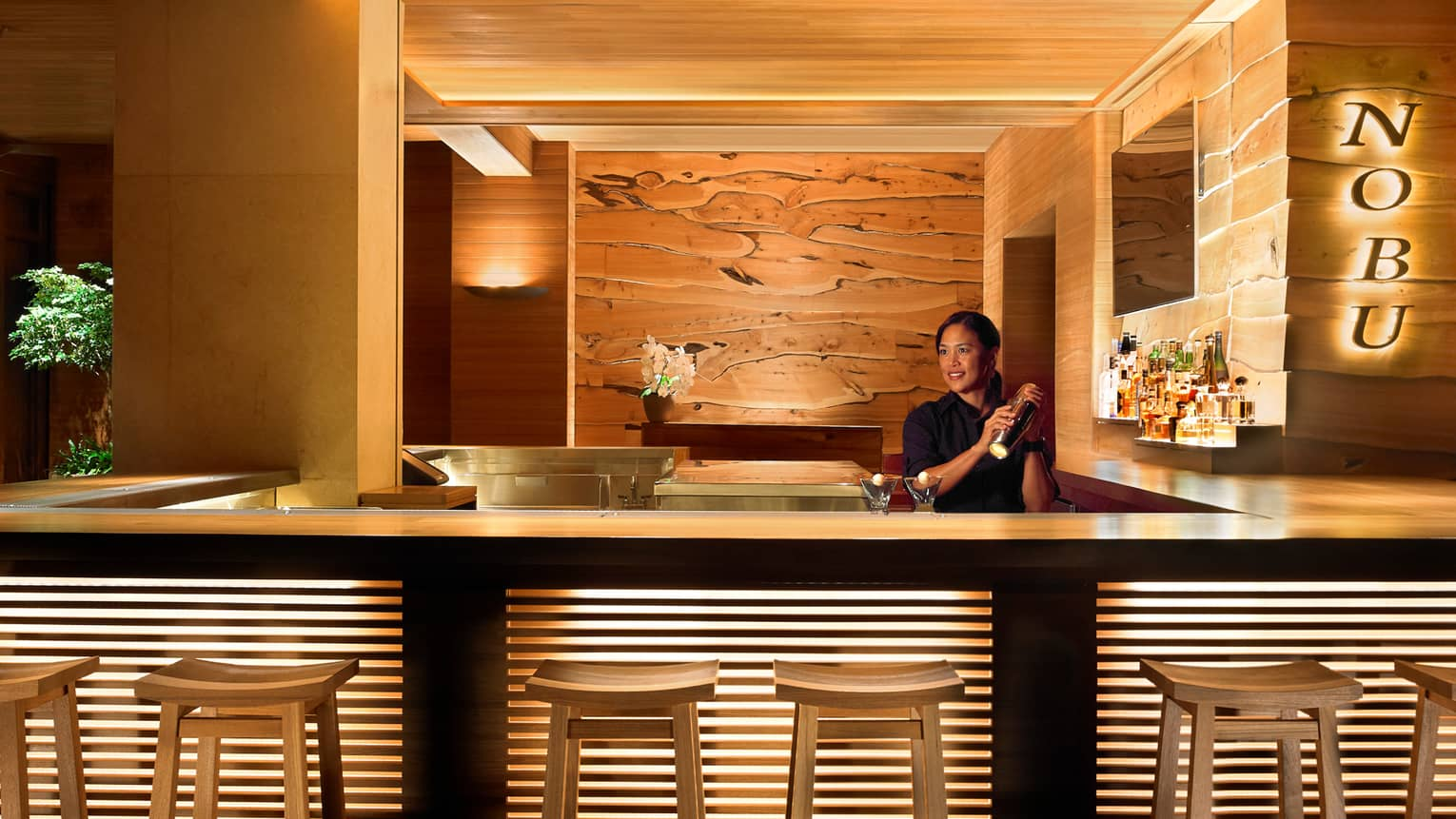 Bartender shaking cocktail behind stool-lined bar at NOBU
