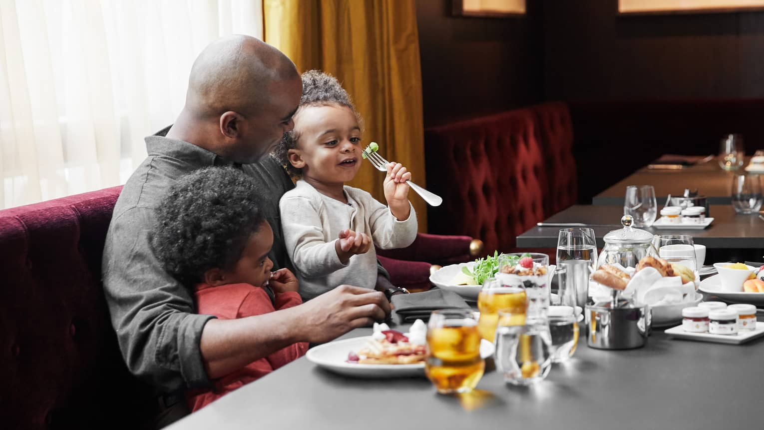 Father eating with his two young children at dining table
