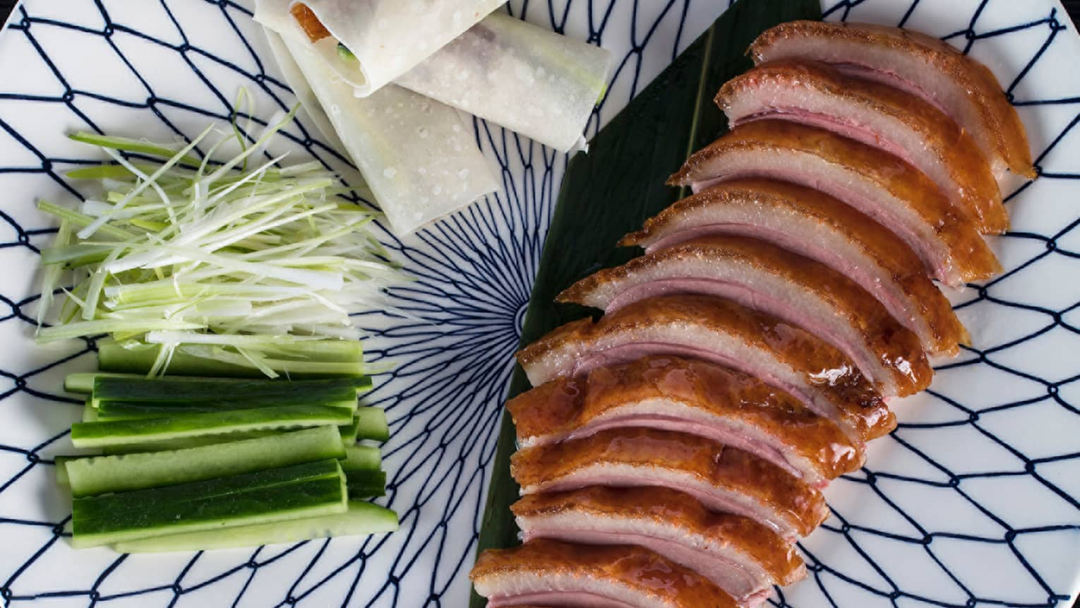 Sliced Peking Duck on platter with sliced cucumbers, onions, spring rolls