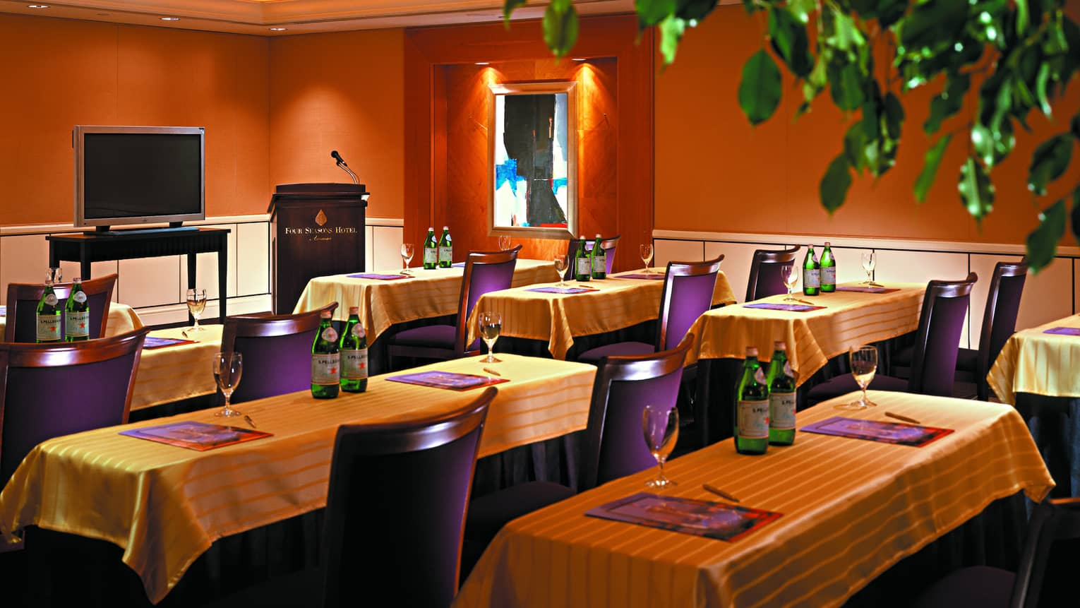 The Crown Room meeting with rows of small tables with gold linens, purple chairs facing small TV and podium
