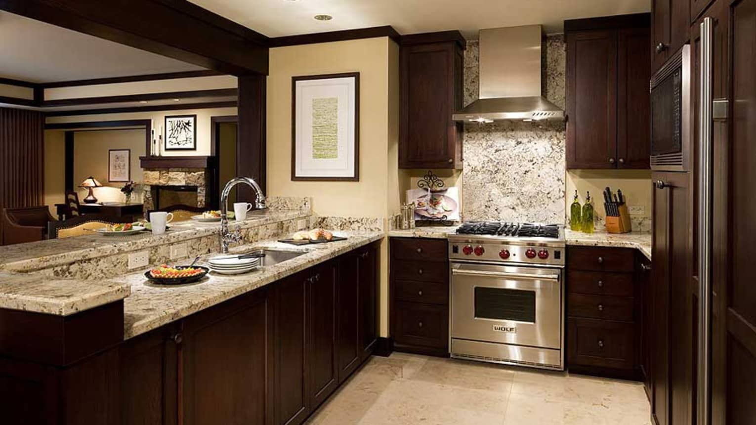 Kitchen with dark wood cupboards, marble counters, stainless steel stove