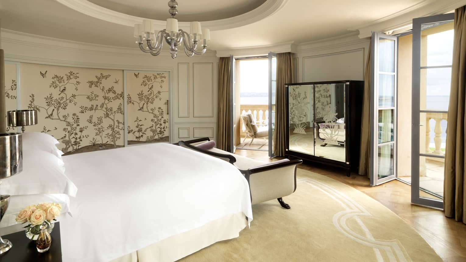 Round hotel room with recessed dome in ceiling, small chandelier, bed with white chaise, mirrored dresser, two patio doors