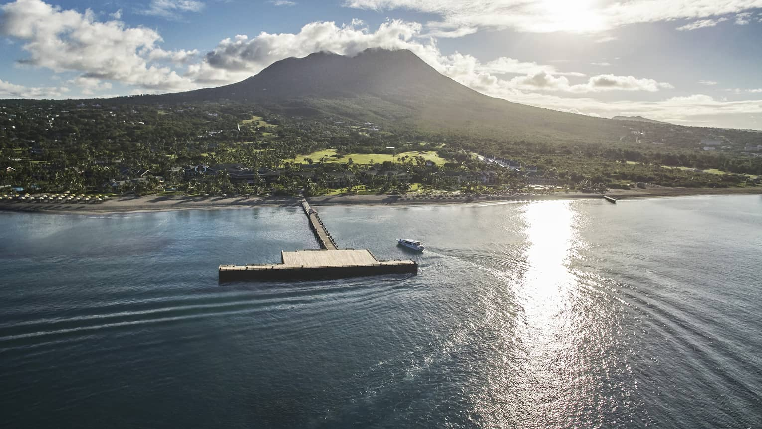 Aerial view of sun shining over Nevis mountain, lagoon with large wood bridge and dock