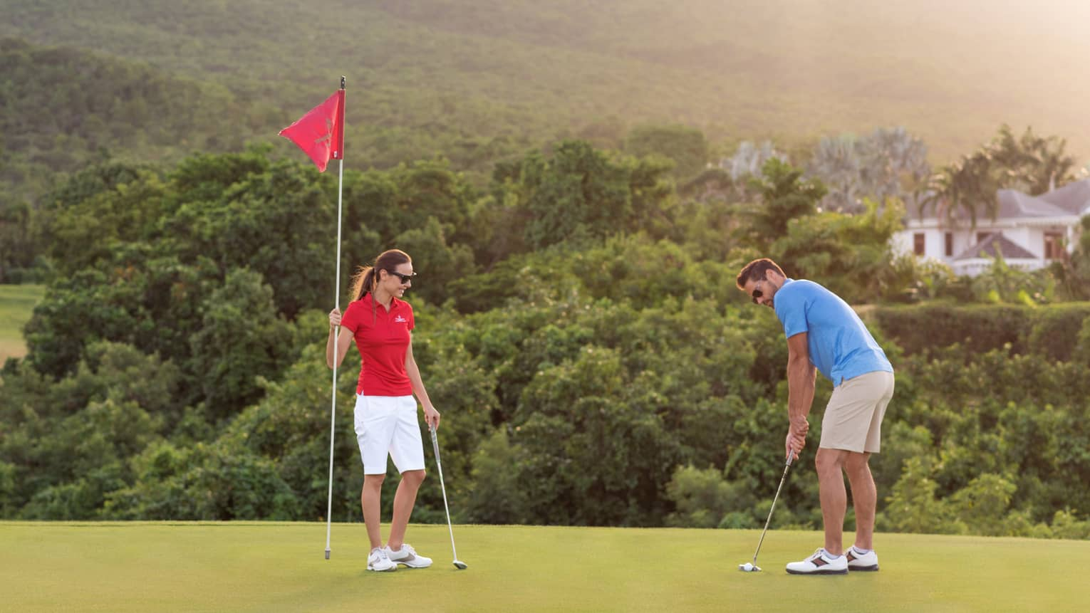 Nevis golf course green on hill, woman holds red flag as man prepares to putt