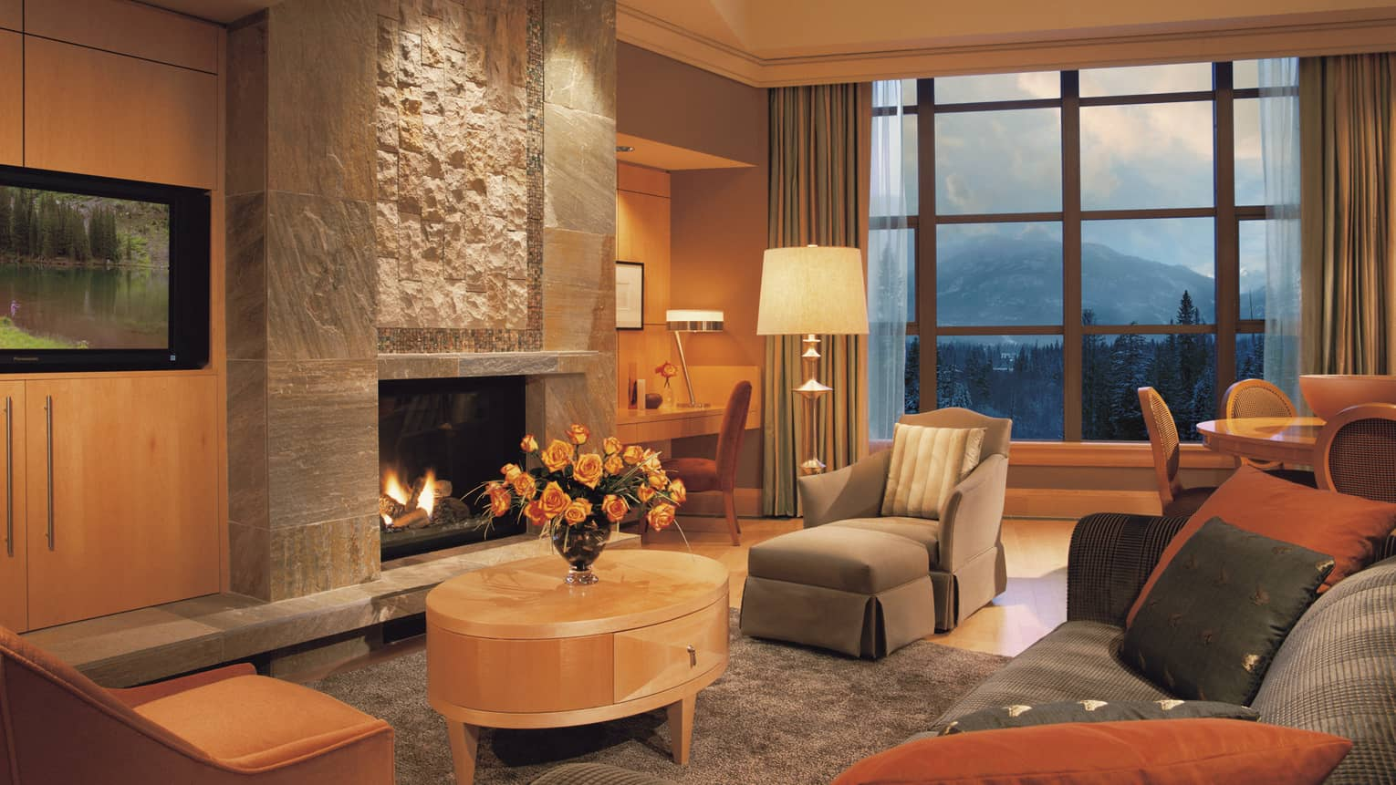 Resort residence living room with grey chaise chair, sofa, table in front of tall stone gas fireplace