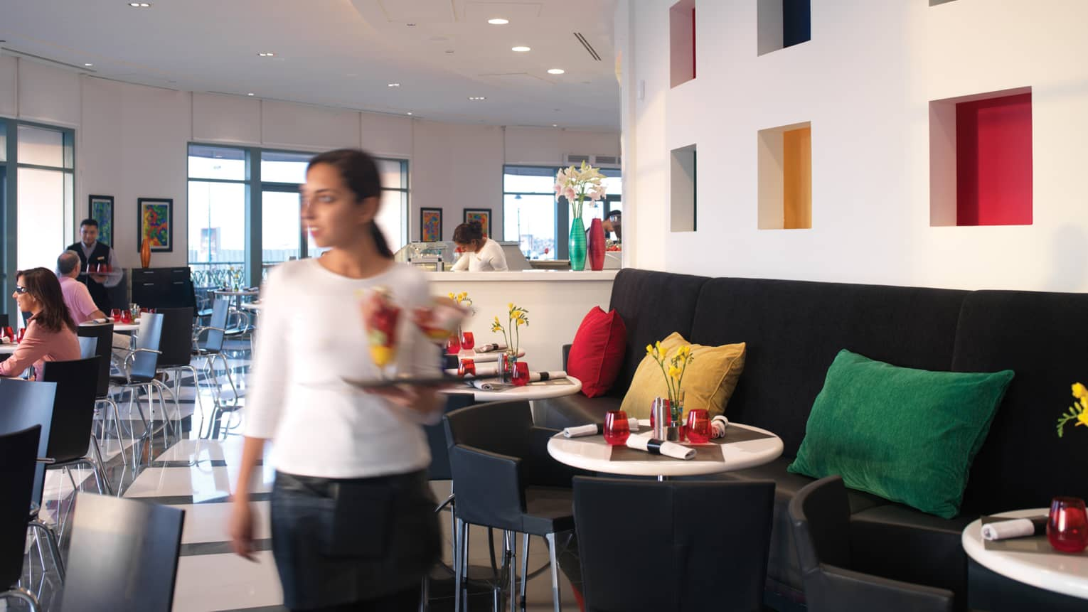 Server with tray of colourful drinks walks through sunny dining room of Fresca Café and Gelateria