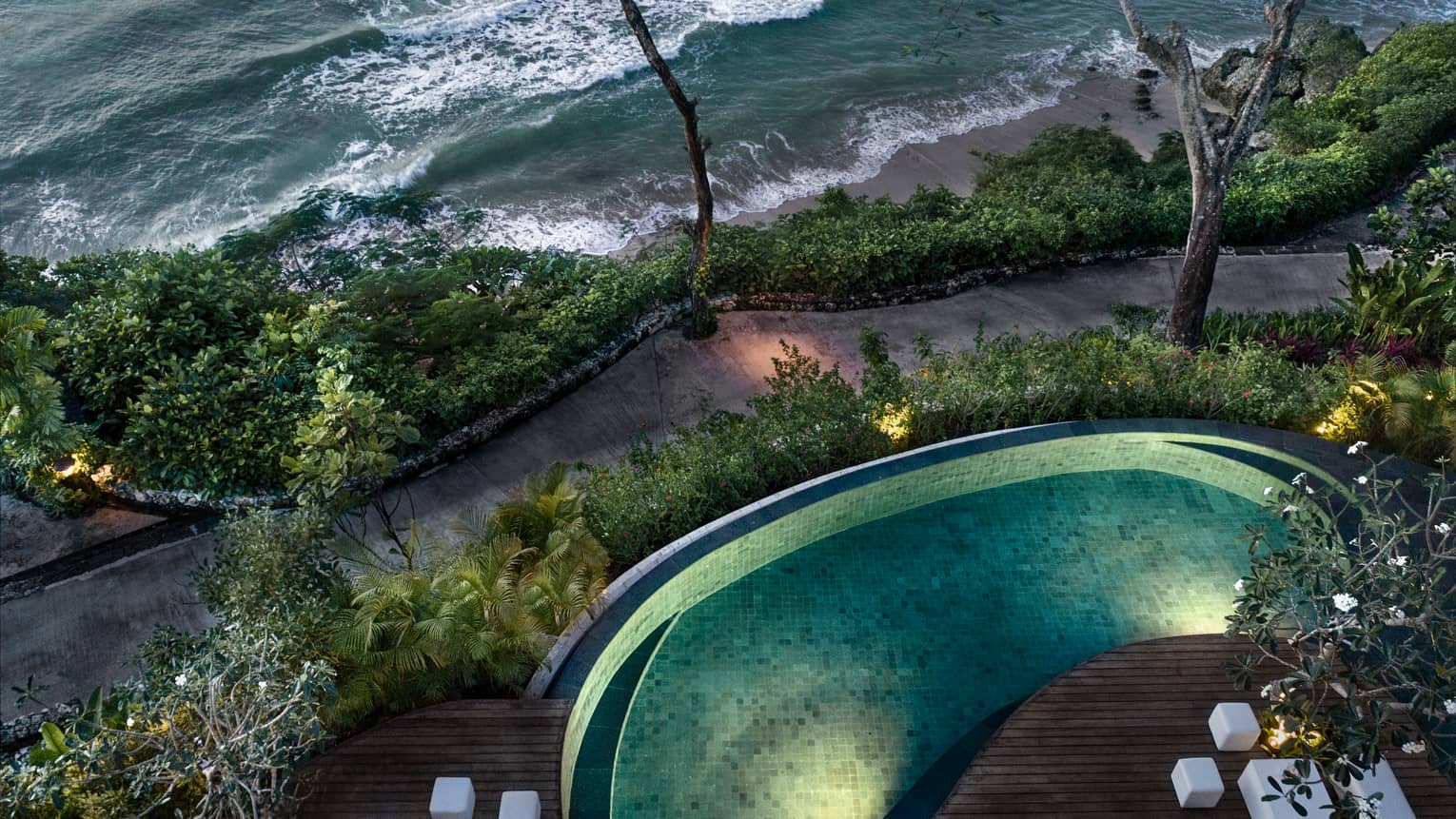Aerial view of illuminated Imperial Villa swimming pool at night, path and ocean waves below