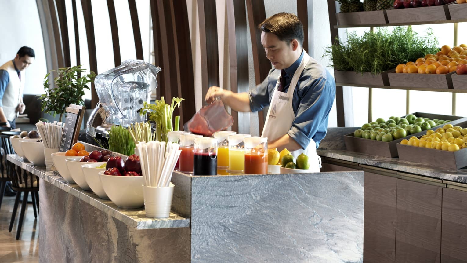 Hotel staff wearing apron pours smoothie from blender in front of counter with fresh fruit, juice