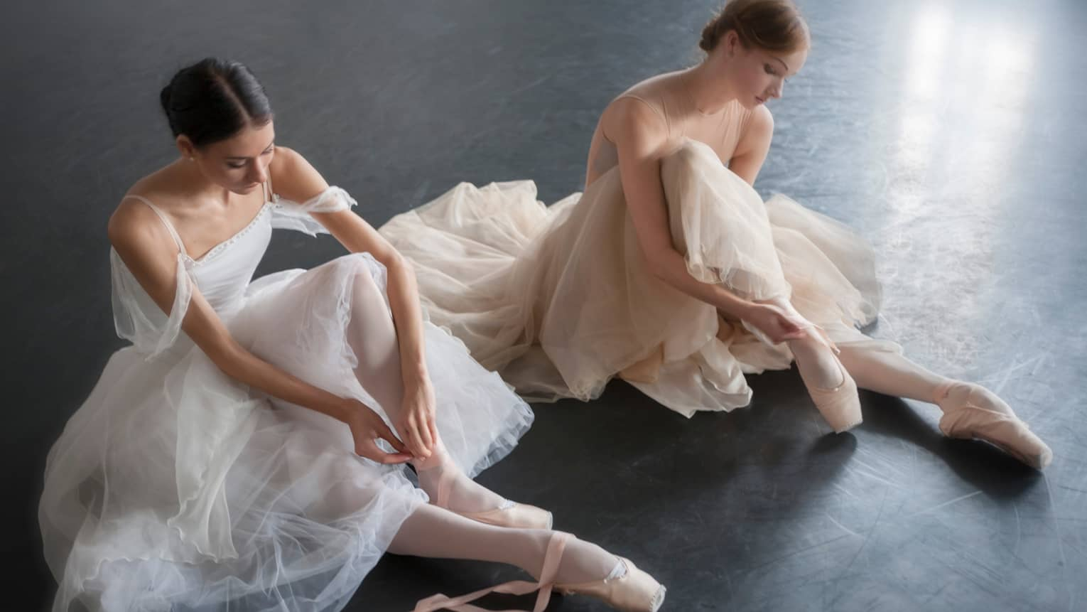 Two ballerinas in long dresses sit on floor, lace up ballet shoes at Mikhailovsky Theatre