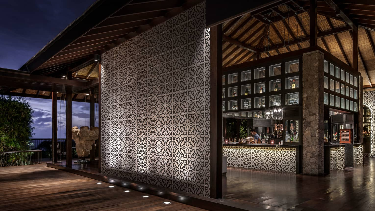 Bar interior, showing mosaic wall and mosaic lined bar with bartender and evening views out window