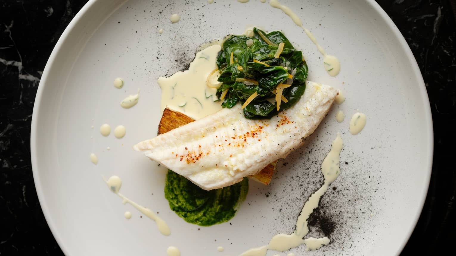 Dover Sole fish fillet with creamed greens, hollandaise sauce on plate