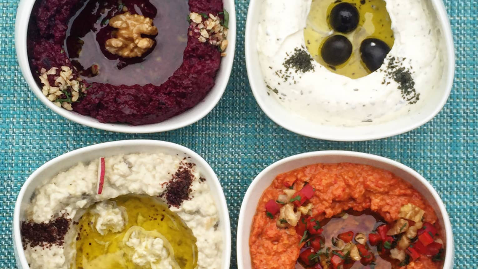 Four bowls with different flavours of hummus, black olive, sesame seed, pomegranate and paprika