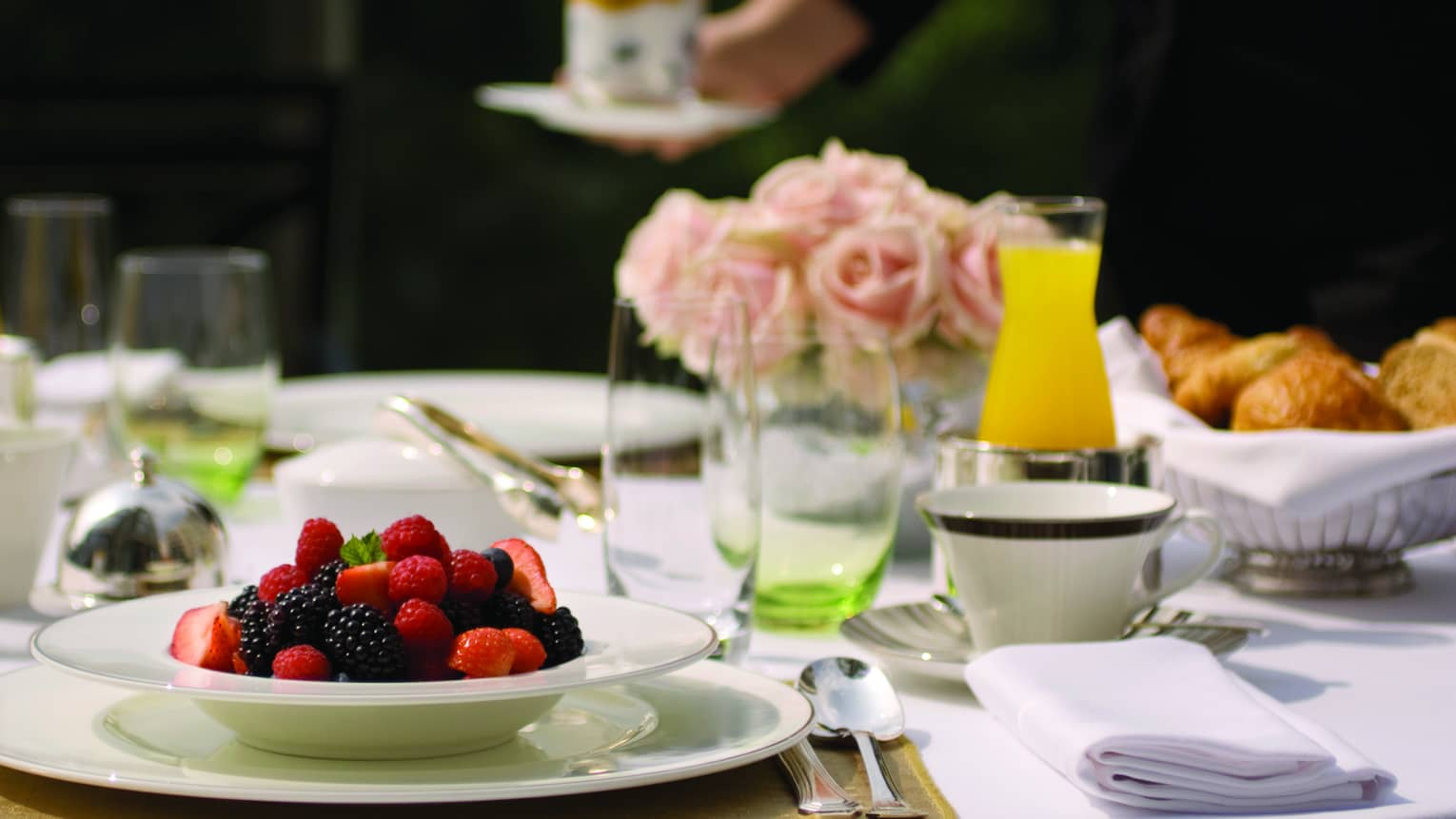White bowl filled with fresh strawberries, blueberries and blackberries on table with glasses, orange juice, pink roses