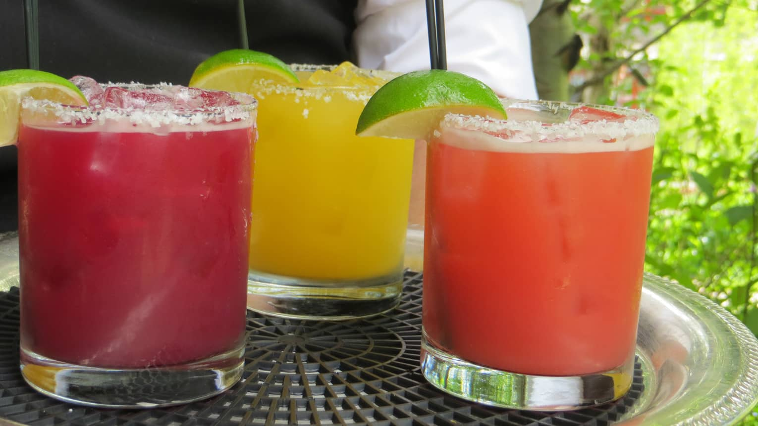 Colourful red, pink and orange margaritas in cocktail glasses with lime wedges on tray