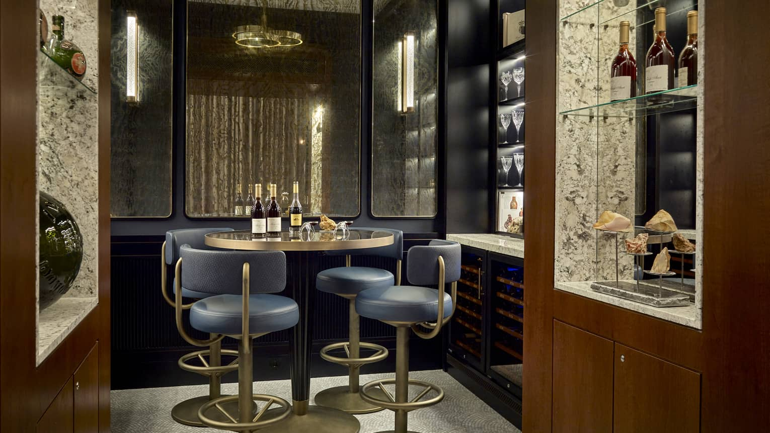 Dark private lounge area with navy and gold barstools at round high-top gold table, wine bottles