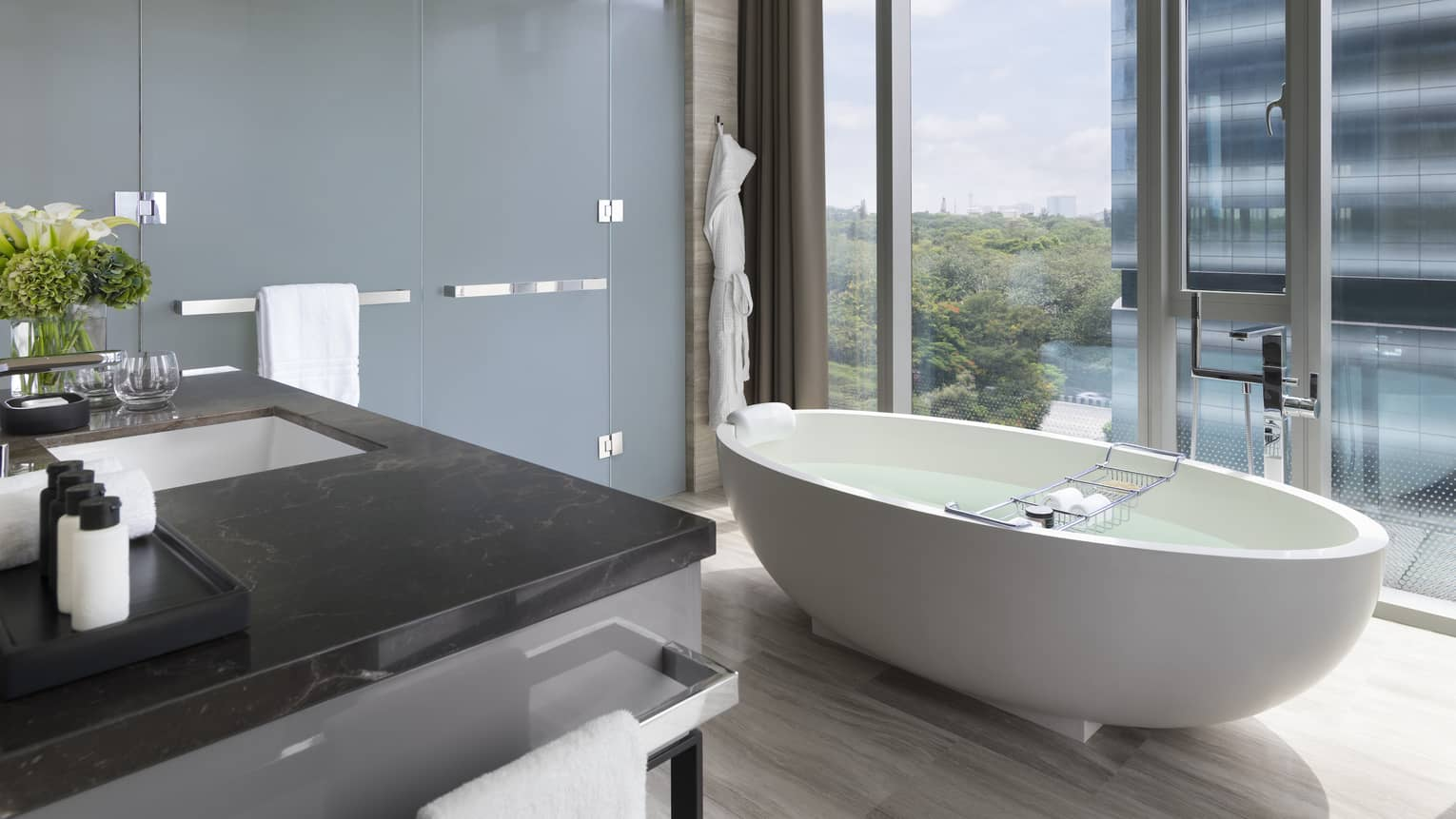 Bathroom with white free-standing tub set next to a floor-to-ceiling window