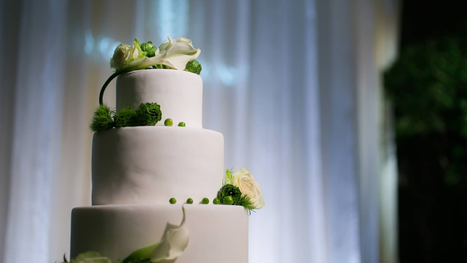 Tiered white wedding cake decorated with white and green flowers