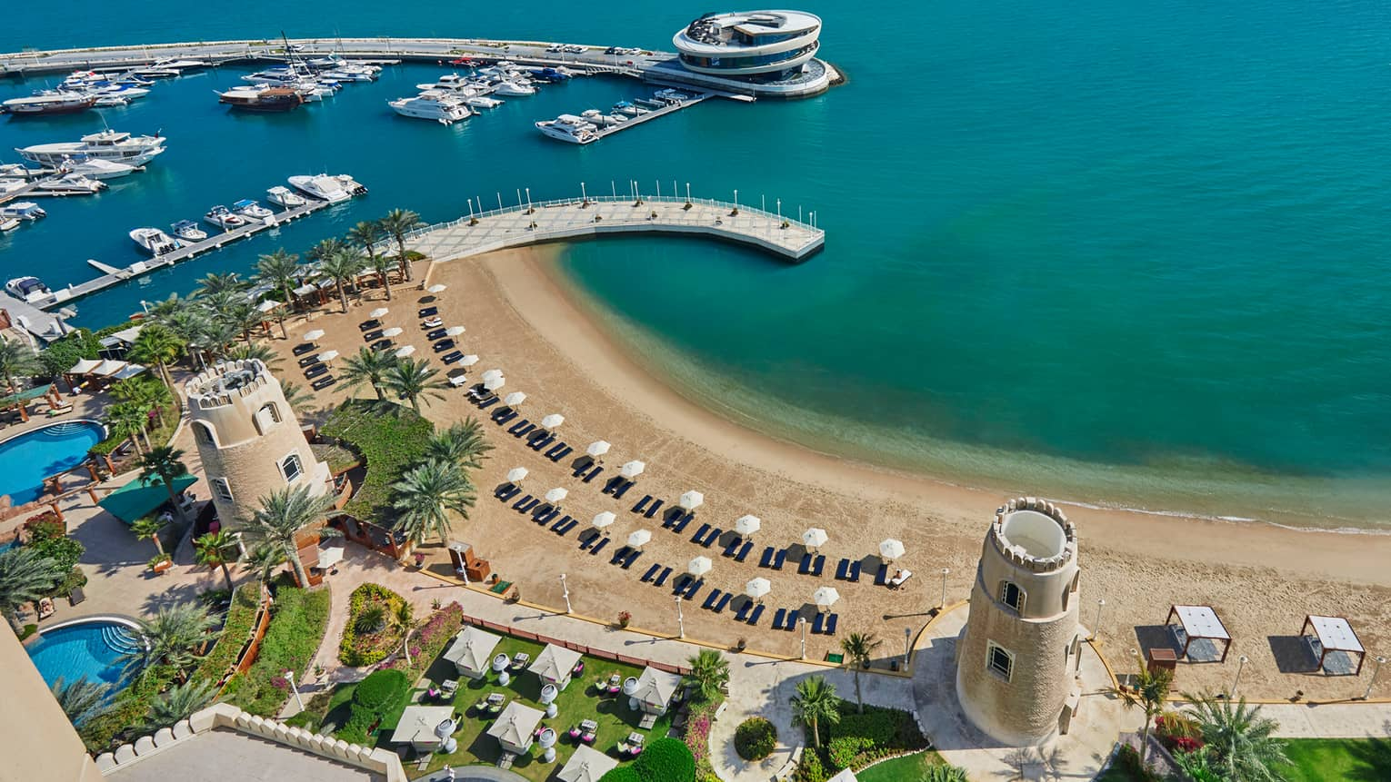 Aerial view of Four Seasons Doha pools and resort grounds, beach and gulf on sunny day