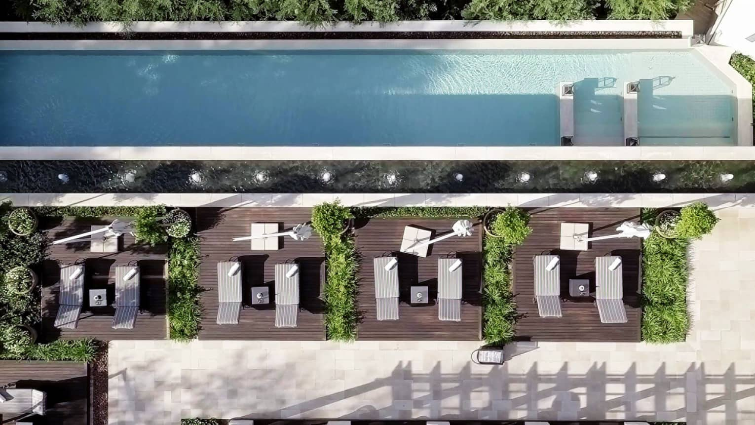 Aerial view of long rectangular outdoor swimming pool, lounge chairs on wood deck