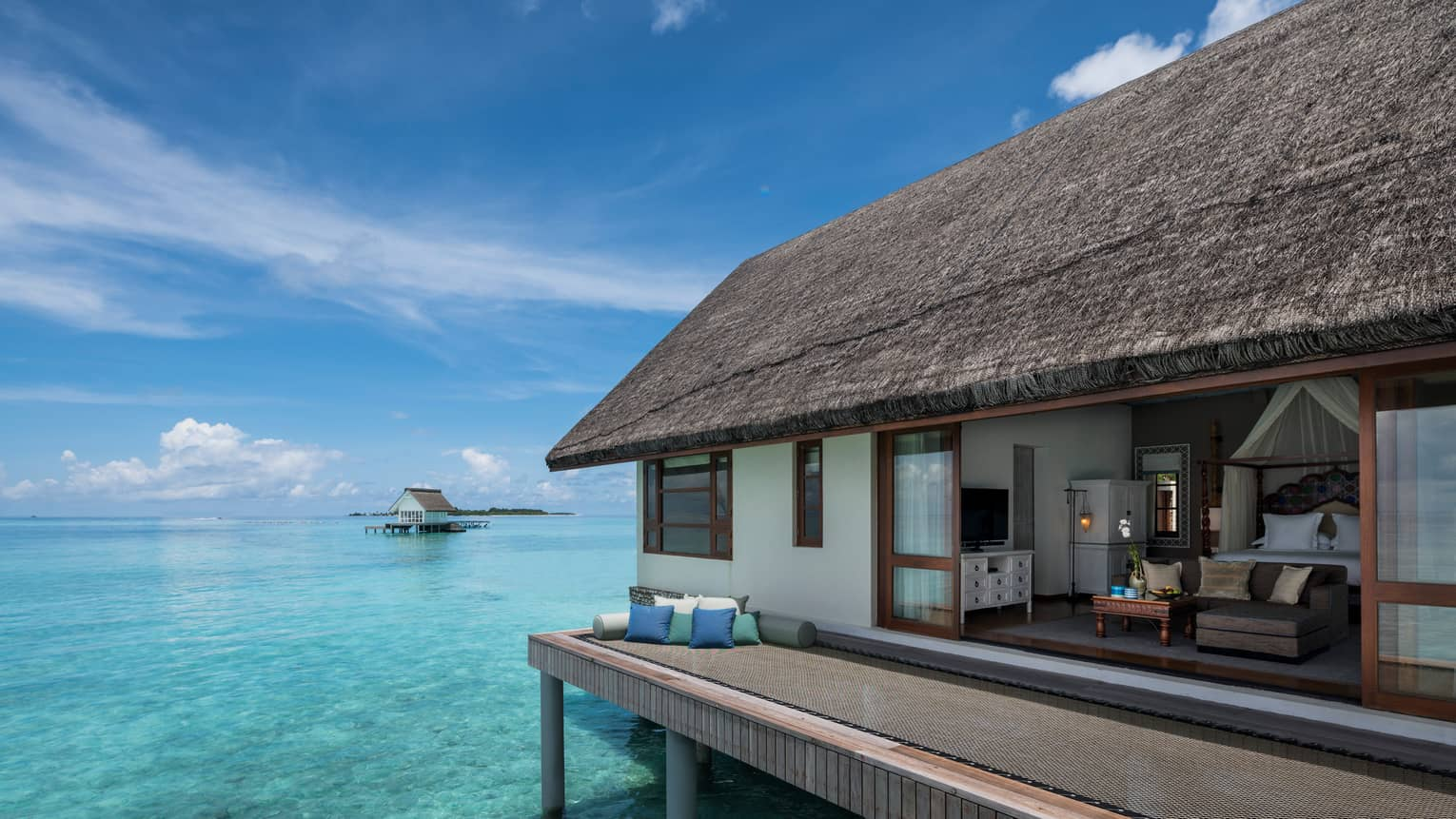 Overwater bungalow with thatched roof, set atop clear turquoise water
