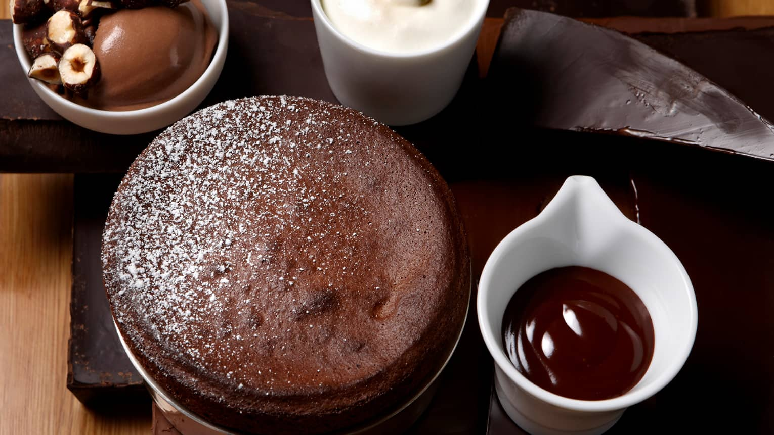 Round dark chocolate soufflé, white dish with warm ganache