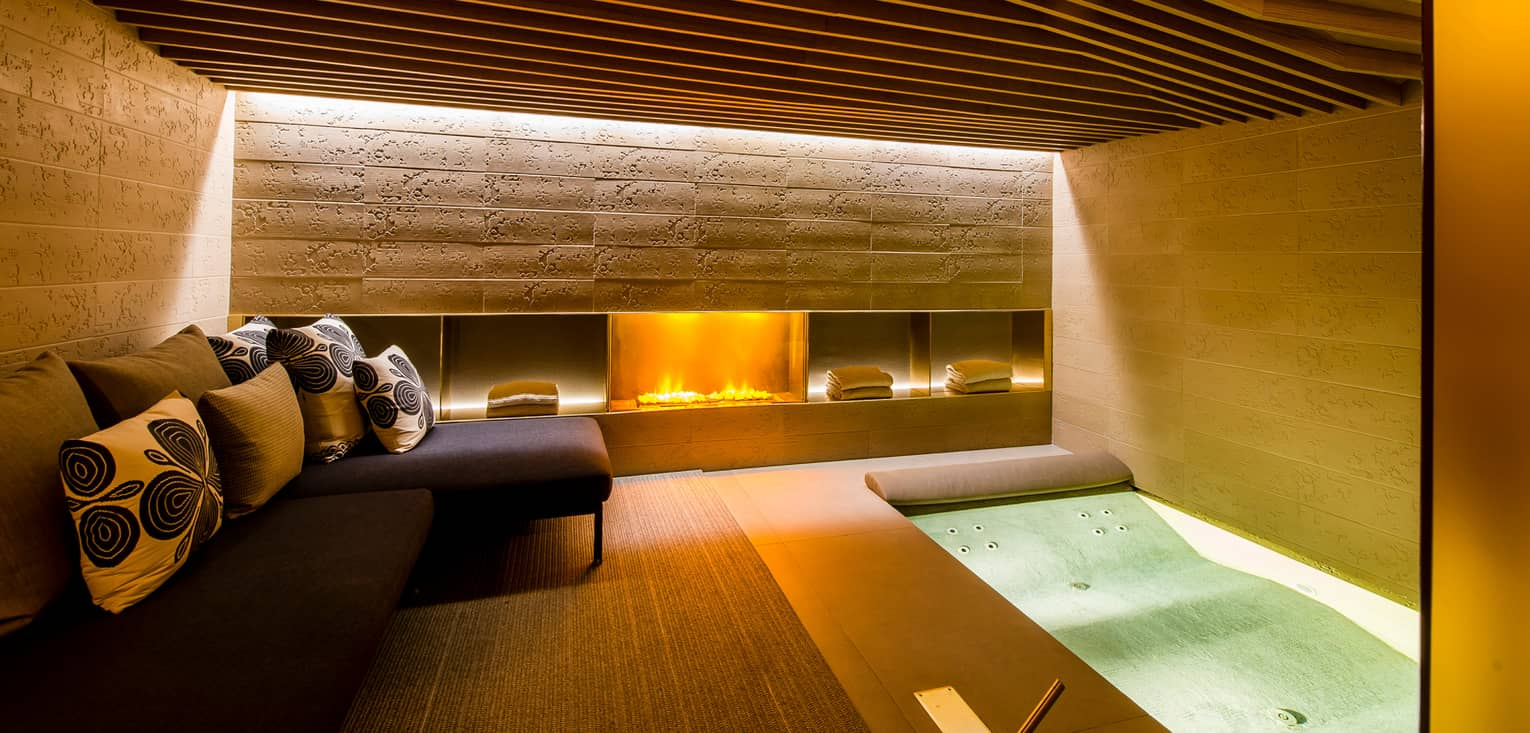 Gas fireplace in under stone wall in Urban Spa, small L-shaped sofa, cushions, spa tub