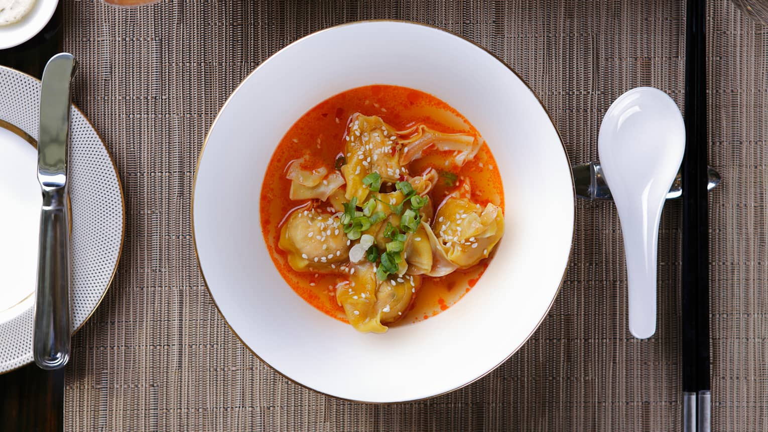 In-room dining white bowl with dumplings in red sauce, sprinkled with white sesame seeds, green onions